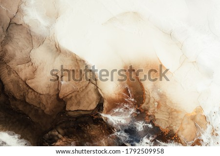 Photo of  Marble texture art background. Alcohol ink water. White brown beige mineral stone design decor banner. Creative abstract gold metallic fleck sand land streak pattern. Luxury stained surface.