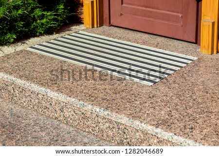 marble threshold with a foot pad at the entrance to the wooden door, close-up.