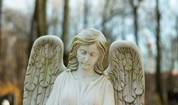 Marble white female angel with wings with blurry background.
