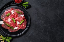 Marbled beef carpaccio with arugula and parmesan cheese. Black background. Top view. Space for text