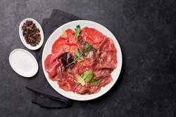 Marbled beef carpaccio with arugula, lemon and parmesan cheese. Top view, flat lay with copy space