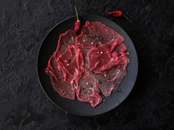 Marbled beef carpaccio with lemon, olive oil and Parmesan cheese on a black slate background. Top view, with copy space