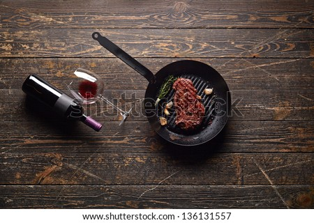 Marbled beef steak in a grill pan with a bottle of wine and wine glass on old wood background. Juicy food background.
