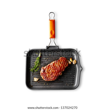 Marbled beef steak with herbs and spices in a grill pan. Isolated on white background.