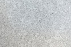 Marbled pattern of a smooth light gray stone slab in closeup