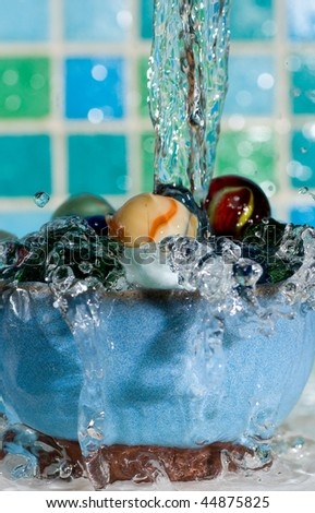 Marbles in a dish with water splashing