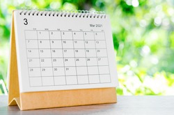 March 2021 Calendar desk for organizer to plan and reminder on wooden table on nature background.