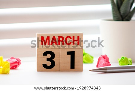 MARCH 31st. Image of MARCH 31 wooden color calendar on white wood wall background. empty space for text Zdjęcia stock ©