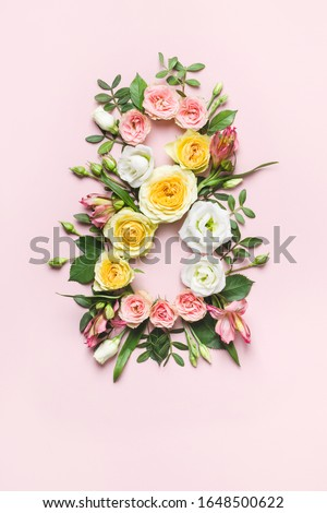 March 8th concept. Creative layout made of colorful rose flowers on pink background. Greeting Card Women's Day on March 8th.