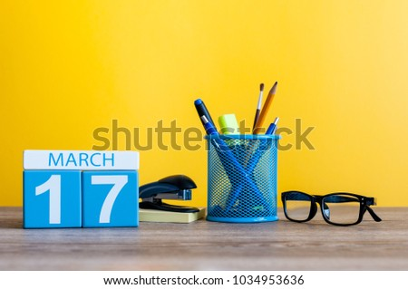 March 17th. Day 17 of march month, calendar on table with yellow background and office or school supplies. Spring time