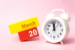March 20th. Day 20 of month, Calendar date. White alarm clock on pastel pink background. Spring month, day of the year concept