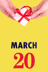 March 20th. Festive Vertical Calendar With Hands Holding White Gift Box With Red Ribbon And Calendar Date 20 March On Illuminating Yellow Background. Spring month, day of the year concept.