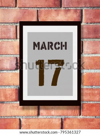 March 17th. 17 March calendar on the wood photo frame with brown brick background. First spring day