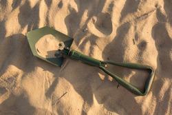 marching shovel. shovel in the sand. green shovel. sand. desert. army shovel