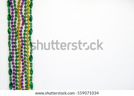 Mardi Gras beads, masks and banner reading  Mardi Gras in traditional festive colors on a white background in horizontal or landscape format with lots of copy space