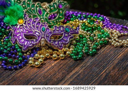 Mardi Gras color beads with masks on wooden table in sunlight Stockfoto ©