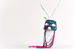Mardi Gras mask and beads on a white animal with horns statuette