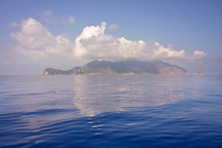 Marettimo island in the middle of the calm sea under a white cloud