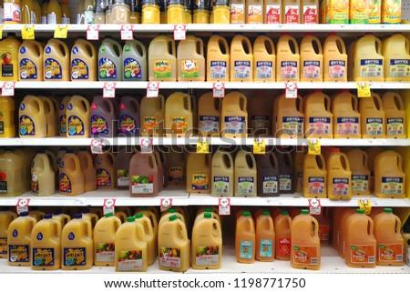 MARGARET RIVER, AUSTRALIA - JUNE 16, 2018:  Various brand orange juice bottles on shelves in Coles supermarket. Coles is an Australian supermarket, retail and consumer services chain. #1198771750