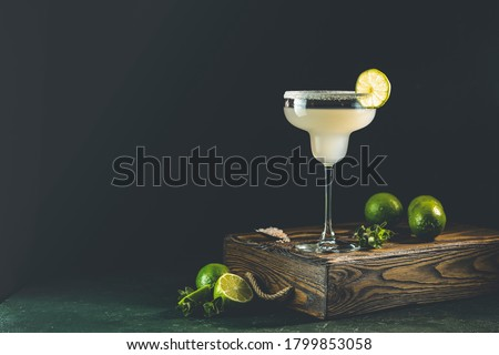 Margarita cocktail with lime and ice on minton dark wooden table with amazing backlight, copy space. Classic Margarita or Daiquiry Cocktail.