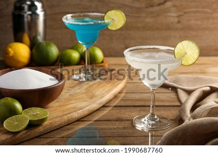 Margarita cocktail with lime and salt on wooden table background. Cocktails drink concept.