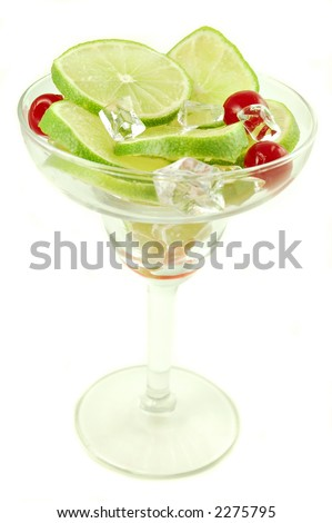 Margarita glass filled with sliced limes and cherries isolated on a white background