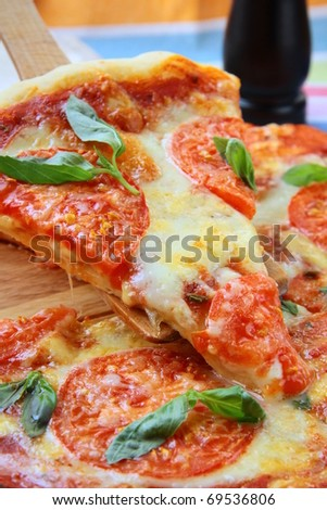 Margarita pizza with tomatoes and basil cheese on the board - stock photo