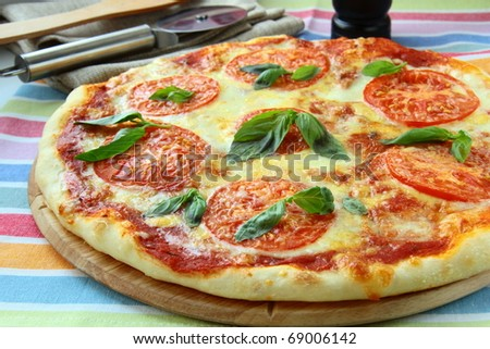 Margarita pizza with tomatoes cheese  and basil on the board