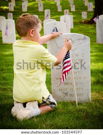 MARIETTA, GA - MAY 26: An unidentified boy straightens a flag on a veteran\'s grave on May 26, 2012, for Memorial Day Weekend at the National Cemetery in Marietta, Ga.