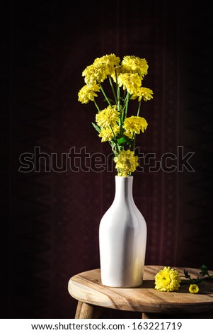 Marigold flower in white vase set on wooden table
