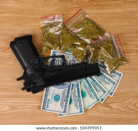 marihuana in packages, dollars and handgun on wooden background