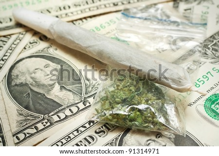 Marijuana cigarette and dry cannabis in sack on dollar banknotes.