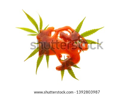 Marijuana extract shatter with marijuana leafs, isolated on white background. Medical marijuana, herbal remedy.