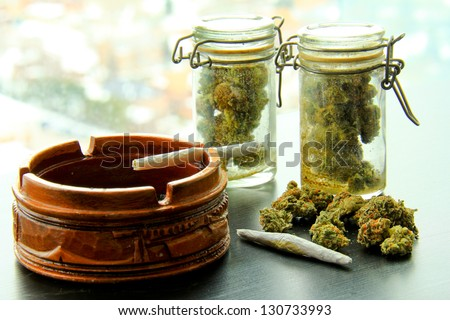 Marijuana Joints and Jars of Weed. A marijuana joint in an ashtray, with another joint, a pile and two jars full of more marijuana.