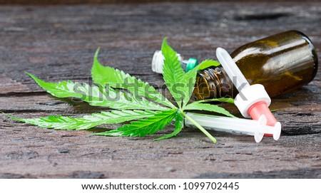 Marijuana leaves  Marijuana extract in capsules and wooden background.