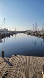 Marina on inner coastal waterway off the ocean with sail boats and yachts at the dock, mid-afternoon on calm still waters in South Carolina on calm blue hue sky.