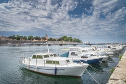 Marina with moored motorboats and sailboats, Zadar bay. Pedestrian bridge Gradski most, walled old town and belltower of Church of St. Donata, Croatia