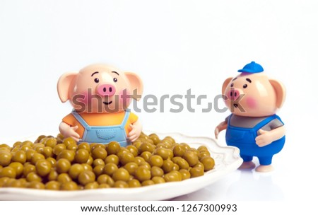 Marinated green peas. Canned peas. Canned green peas. Canned peas in a plate. New Year Yellow pig 2019. Gluttony. Piglet is smiling.