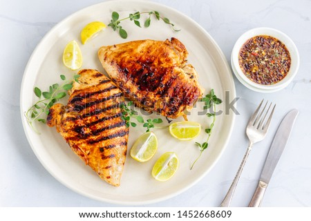 Marinated grilled healthy chicken breasts in a White Plate and served with fresh Oregano on White Background. Сток-фото ©