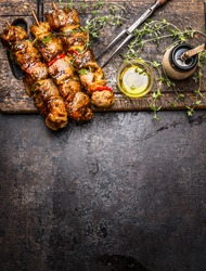 Marinated meat skewers with vegetables for grill or BBQ , fresh seasoning and oil on dark rustic wooden background, top view, place for text, border, vertical