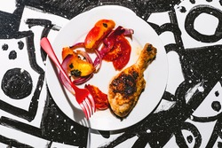 Marinated peach chicken legs on black and white abstract background with floating red fork