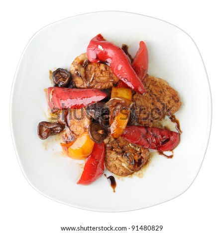 marinated pork with shiitake mushrooms and sweet peppers on white dish isolated on a white background. Top view.