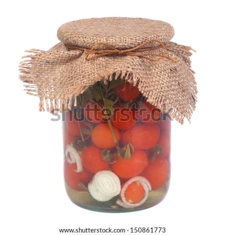 Marinated ripe tomatoes in a glass jar isolated on white background