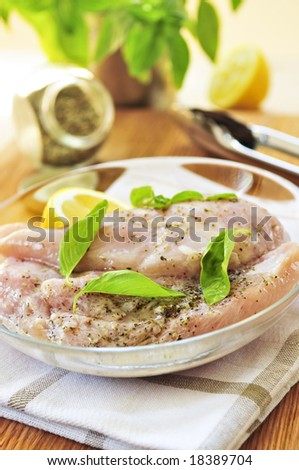 Marinating raw chicken breasts in lemon juice and herbs