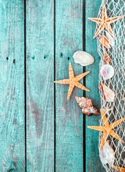 Marine border of fishing net with shells and starfish on rustic turquoise blue wooden planks with a weathered woodgrain texture and copyspace
