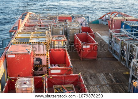 Marine cargo operations, offshore supply boat with containers and tanks onboard delivers cargo to oil rig platform. Calm sea. Dp supplier job. oil and gas research and mining indusrty