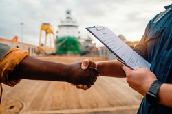 marine contractor businessman handshaking with worker on the ship with contract agreement. Handshake of two boilersuits with different colors wiyh maritime background