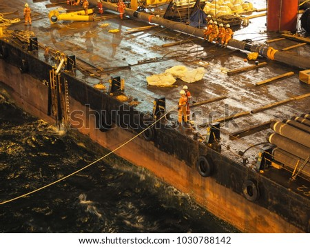 Marine crews working on material barge at night