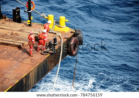 Marine crews working on mooring ropes on cargo barge at offshore