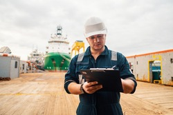 Marine Deck Officer or Chief mate on deck of offshore vessel or ship doing check and filling checklist. Paperwork at sea. Ship is on background